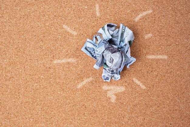 Concept idea of saving money. crumpled 100 dollar bill on cork board background