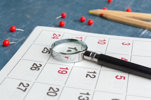 ビジネスおよび会議のコンセプトイメージ。重要な予定と虫眼鏡を思い出させるカレンダー