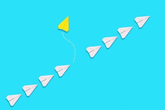 The concept of independence and individuality. a yellow paper airplane flies out of the queue of white planes. blue background. flat lay.