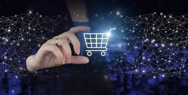 The concept of innovation in e-commerce. hand hold digital hologram cart sign on city dark blurred background. online shopping or internet shop concepts.