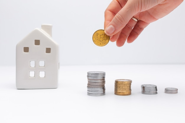 Concept of investment in property hand putting coin with white house on background taking loan