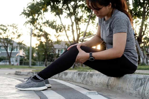 Concept of jogging, an asian woman massaging her knees in a street sitting position.