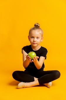 Concept of kid's sports and healthy eating. happy cheerful excited confident gymnast girl is holding a green fresh apple, isolated on vivid yellow background