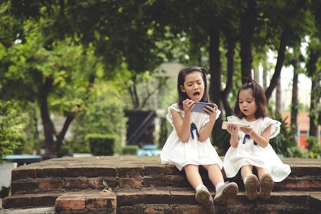 개념 어린이 및 가제트 두 명의 어린 소녀 형제 자매가 전화를 봅니다.