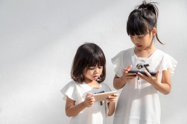 개념 어린이 및 가제트 두 명의 어린 소녀 형제 자매가 전화를 보고 스마트폰을 들고 있습니다.