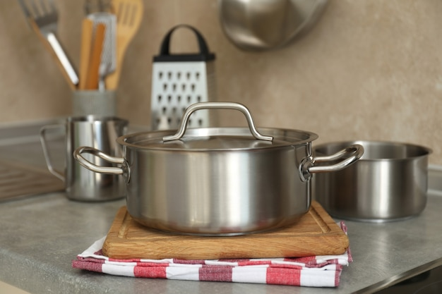 Concept of kitchen utensil with metal pot, selective focus.