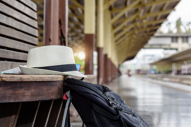 Concept life style holidays travel or journey : old white hat with black backpack put on the wooden bench at the train station.