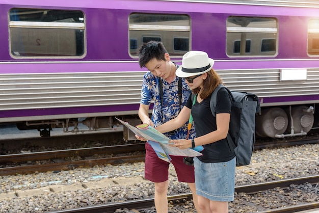 Concept life style travel or journey : young asian couple are viewing map to plan a trip in the train station.