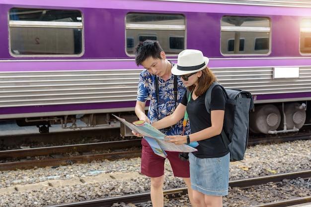 컨셉 라이프 스타일 여행 또는 여행 : 젊은 아시아 부부는 기차역에서 여행을 계획하기 위해지도를보고 있습니다.