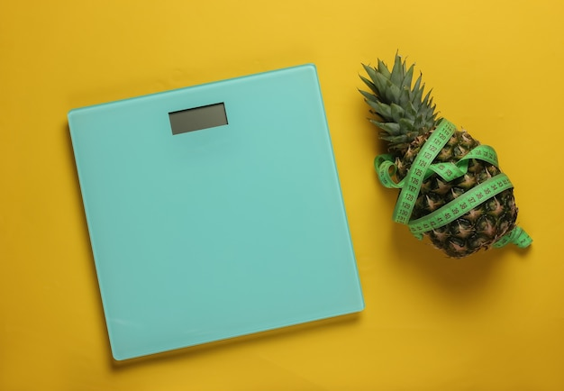 The concept of losing weight. scales, pineapple wrapped with measuring tape on yellow background. healthy eating. top view