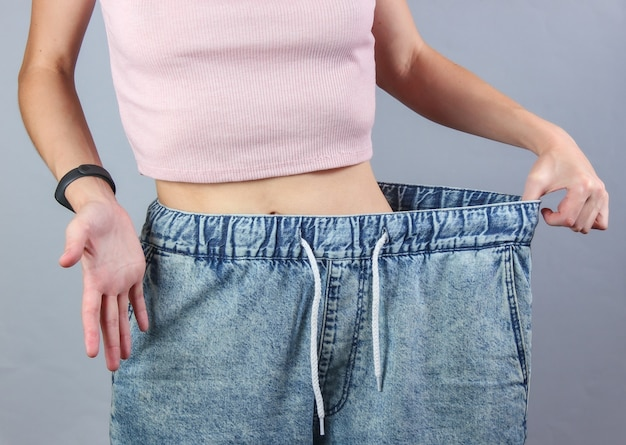 Concept of losing weight. woman in very big jeans on gray studio background.