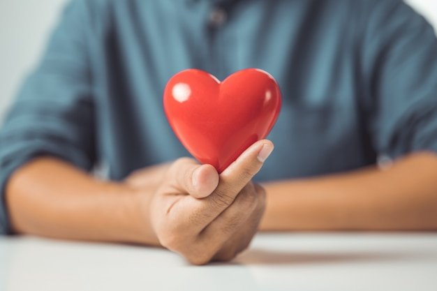 Concept of love male hands holding red heart world mental health day life and health insurance