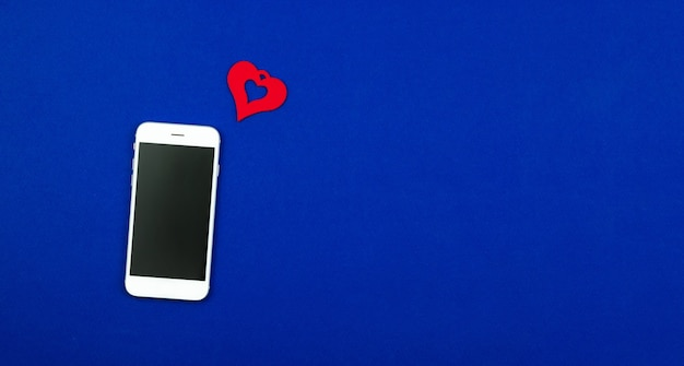 Concept of love message on smartphone, valentine's day heart, new follower, banner design on flat blue background. high quality photo