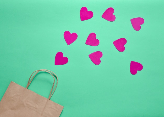 The concept of love of shopping. a paper bag for shopping and lots of decorative hearts on a colored mint background. valentine's day. top view.
