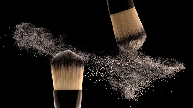 Concept, makeup. two brush makers scatter powder.
