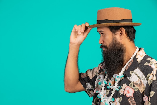 Concept of male tourists who have long beard wearing a hat on a blue .