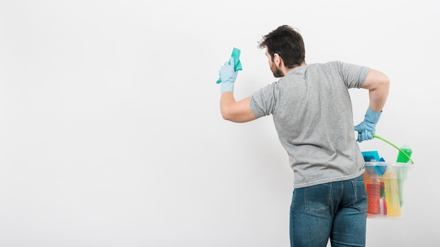 Concept of man cleaning his home with copyspace on wall