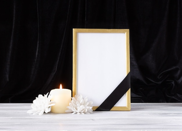 The concept of memory, funerals and condolences. photo frame with black mourning ribbon, candle and flowers.
