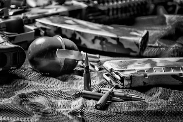 The concept of military ammunition. cartridges for a machine gun, clip, grenade, machine gun. background khaki. mixed media