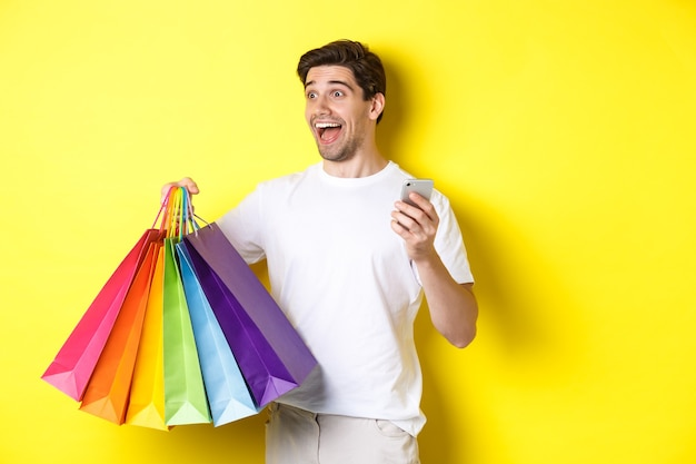 Concept of mobile banking and cashback. happy man looking amazed, holding shopping bags and smartphone, yellow background.