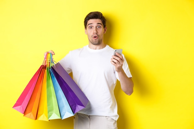Concept of mobile banking and cashback. surprised man holding shopping bags and smartphone, standing over yellow background