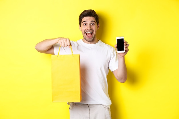 Concetto di mobile banking e cashback. giovane ragazzo felice che tiene la borsa della spesa e che mostra lo schermo dello smartphone, sfondo giallo.