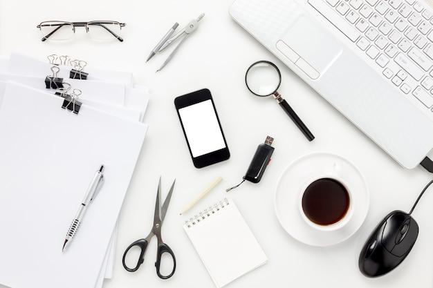 トップビューアクセサリーオフィスデスクconcept.mobile電話、コーヒー、ノートブック、ペン、白いオフィスのデスクでラップトップ。
