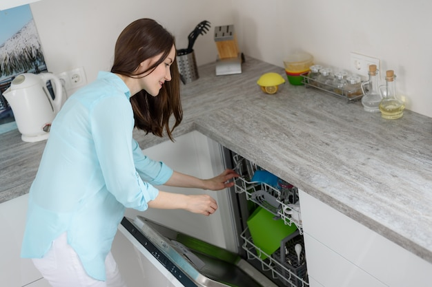 The concept of modern washing dishes, a woman pulls clean dishes from the dishwasher in the white kitchen