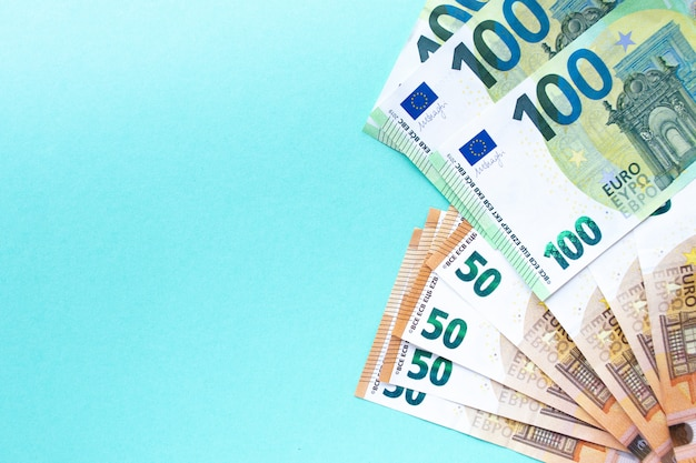 The concept of money and finance. banknotes of 100 and 50 euros laid out on a blue background on the right side. with place for text.