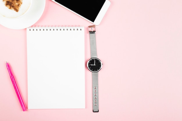 Concept morning planning - cappuccino, notebook, pen, phone, watch on pink space. top view, copy space