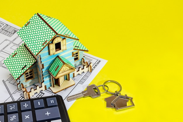 The concept of mortgage and rental housing and real estate. mortgage credit lending. house mock up with keys with blueprint on yellow background. calculator for calculating the cost.