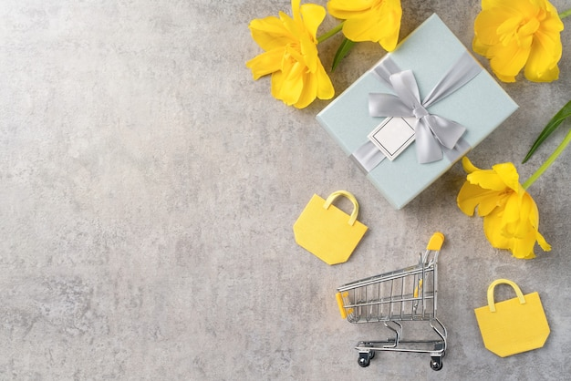 Concept of mother's day holiday gift shopping greeting design with yellow tulip flower bouquet on gray background