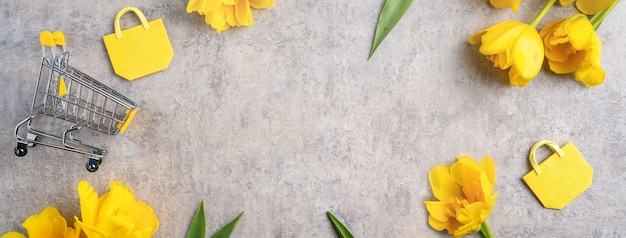 Concept of mother's day holiday gift shopping greeting design with yellow tulip flower bouquet on gray
