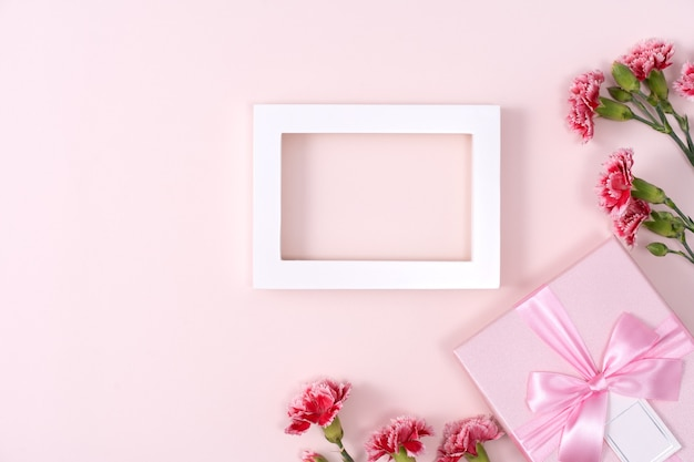 Concept of mother's day holiday greeting background design  with carnations bouquet on pink background
