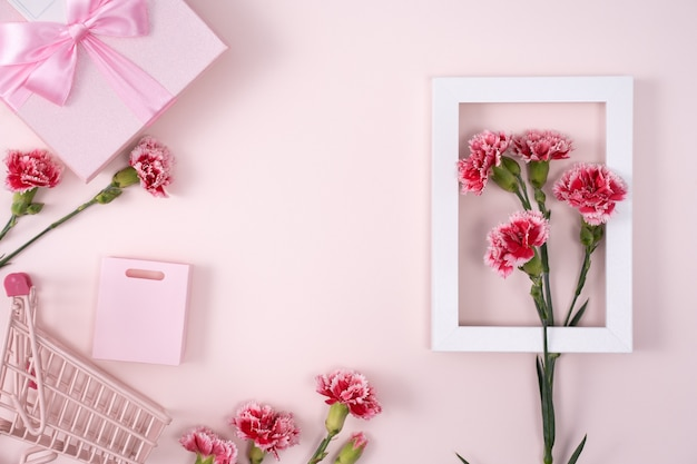 Concept of mother's day holiday greeting design with carnation bouquet and gift on pink background