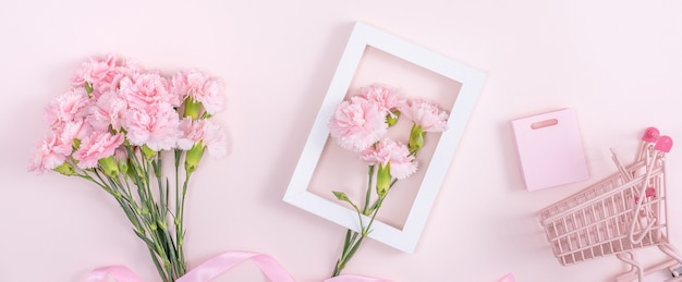 Concept of mother's day holiday greeting design with carnation bouquet and gift on pink surface