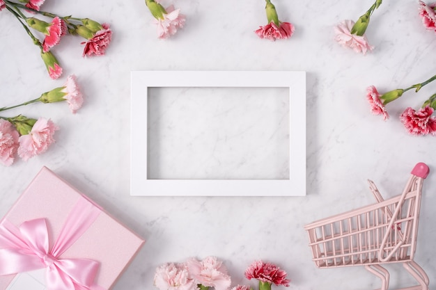 Concept of mother's day holiday greeting design with carnation bouquet and gift on white marble background
