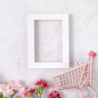 Concept of mother's day holiday greeting design with carnation bouquet and gift on white marble surface