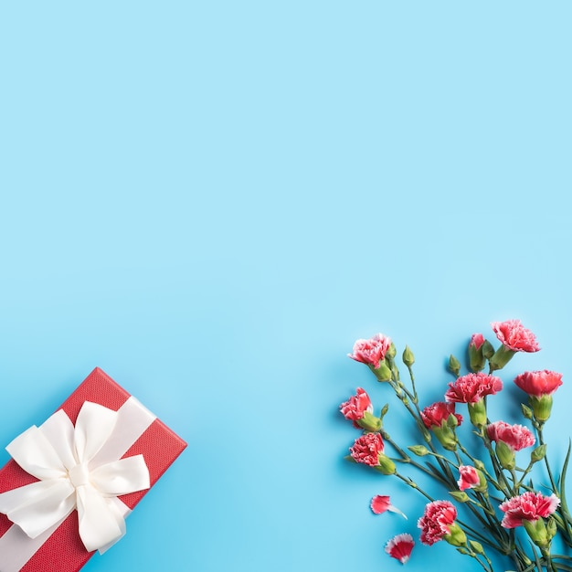 Concept of mother's day holiday greeting gift design with carnation bouquet on bright blue table background Premium Photo