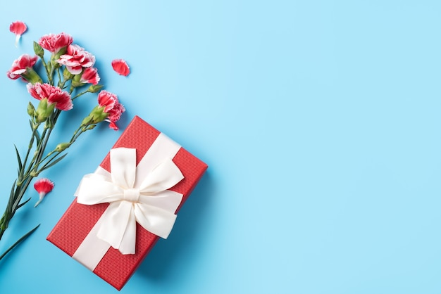 Concept of mother's day holiday greeting gift design with carnation bouquet on bright blue table background
