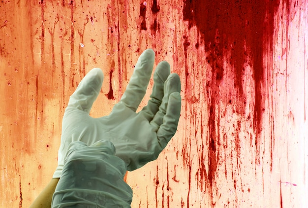 Concept of murder bloody on wall and human hand with rubber gloves.