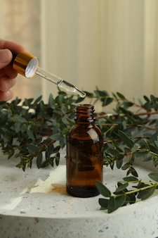 Concept of natural cosmetics with female hand dripping eucalyptus oil