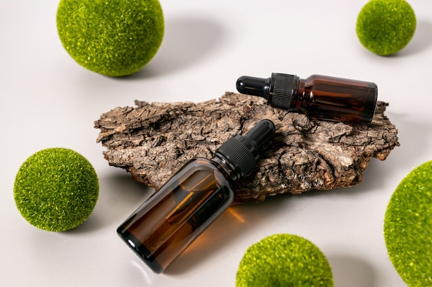 Concept of natural skin care cosmetics. essential oil or dark glasse serum on a tree bark with green balls. natural eco friendy concept for cosmetics brand.