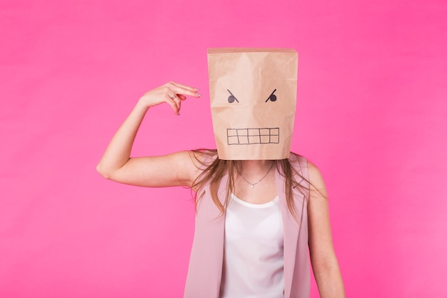Concept of negative emotions - angry woman with a paper bag on his face.