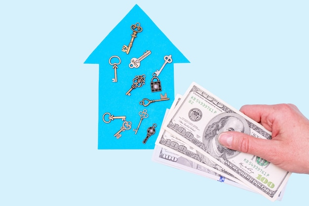 The concept of a new home, mortgage, loan. dream home concept. woman's hand holds dollars over a blue paper house model and keys on a pastel background, mock up, copy space, top view
