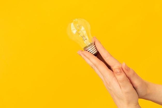 革新と創造性とコンセプトの新しいアイデア、女性の手はオレンジ色の背景に電球を保持します