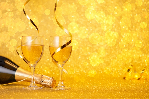 Concept of the new year. a bottle of champagne and groceries on a gold wall