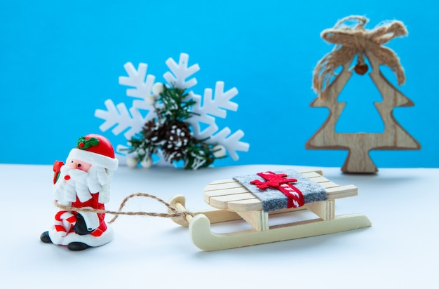 The concept of the new year holidays. santa claus with a sleigh on a light blue background