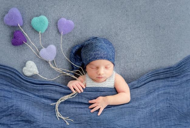 Концепция новорожденного мальчика младенца спящего, покрытого синим одеялом