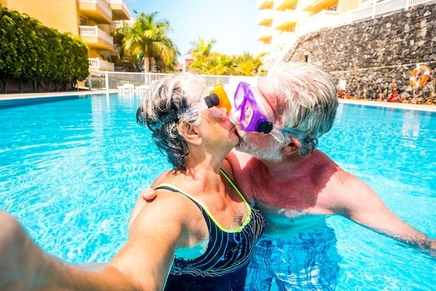 Concept of no limit age and relationship with couple of caucasian happy senior old people kissing together in the pool having fun during summer holiday vacation
